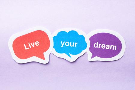 metas: Vive tus concepto de sueño burbujas de papel contra el fondo morado.