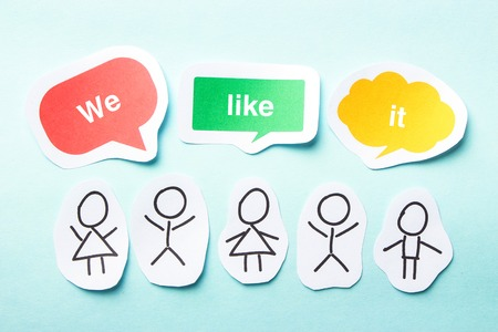 we the people: Happy paper people with speech bubbles of We like it text on the blue background. Stock Photo