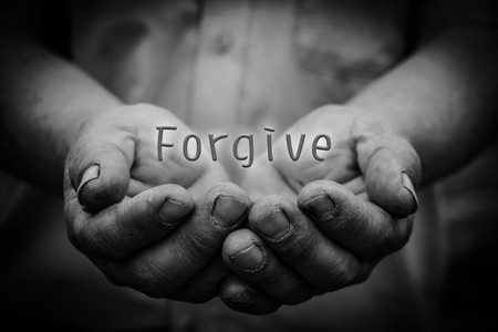 Forgive text is in the holding hands with dark corners. Stock Photo