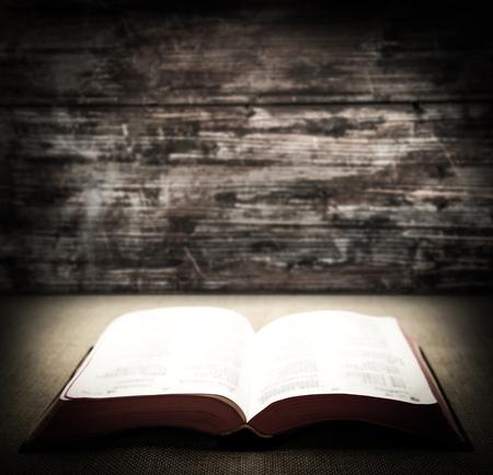 biblia: Abra la biblia está tumbado en la mesa con el fondo de madera. Foto de archivo