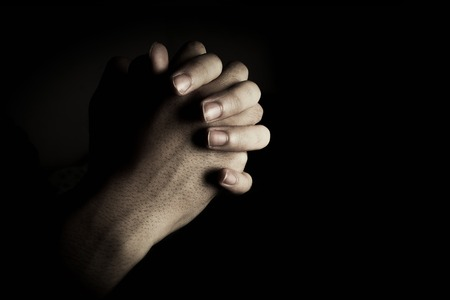 clasps: Praying hands is in the dark with light on the hands.