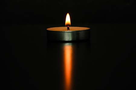 A candle is on the dark black background.