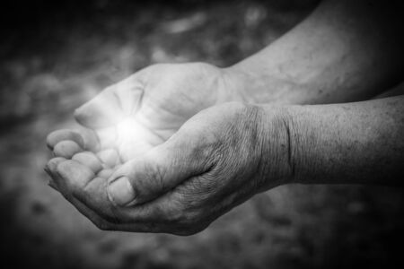 praise hands: Light is in the holding hands with dark corners.
