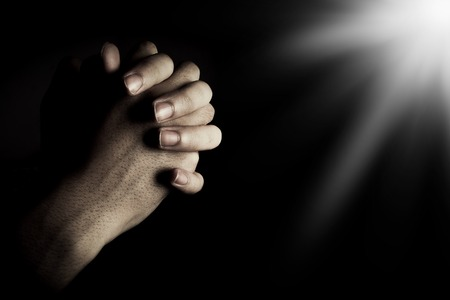 confession: Praying hands is in the dark with light on the hands.