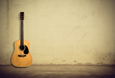 Acoustic guitar against old style wall