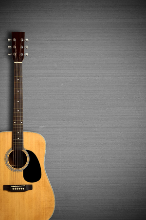 frets: Acoustic guitar on the gray wall. Stock Photo