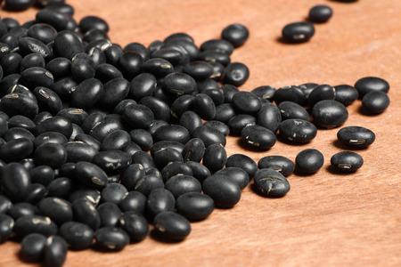 turtle bean: Some black beans is on the wooden background.