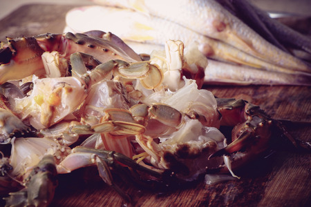 blue swimmer crab: Cut or prepared crab and fish is on the cutting board. Stock Photo