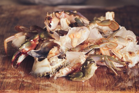 blue swimmer crab: Cut or prepared crab is on the cutting board.