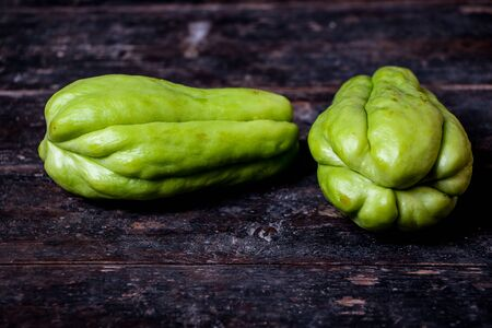 chayote: Green chayote is on the old wooden background.