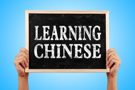 chinese adult: Hands holding blackboard with text Learning Chinese against blue background.