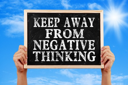 negative thinking: Hands holding blackboard with text Keep Away From Negative Thinking against blue sky background. Banque d'images