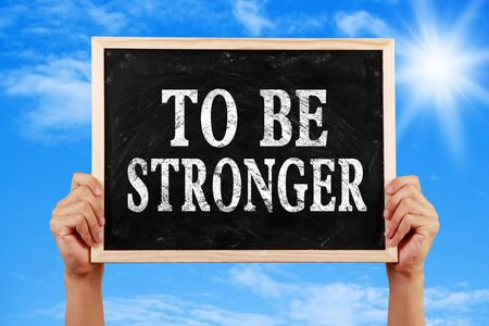 stronger: Hands holding blackboard with text To Be Stronger against blue sky background. Stock Photo