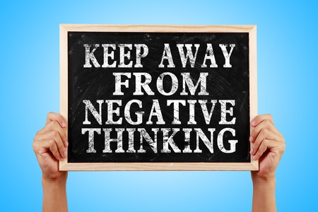 negative thinking: Hands holding blackboard with text Keep Away From Negative Thinking against blue background. Stock Photo