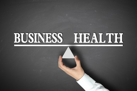 health equity: Business Health Balance concept with scale holden by businessman hand against the blackboard background. Stock Photo