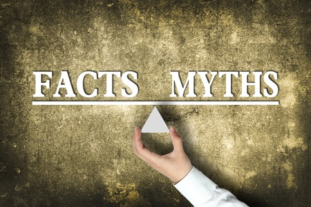 myths: Facts Myths Balance concept with scale holden by businessman hand against the old background. Stock Photo
