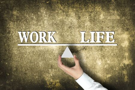health equity: Work Life Balance concept with scale holden by businessman hand against the old background. Stock Photo