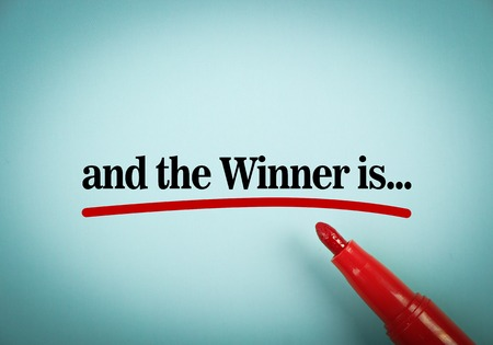 Text And the winner is with red underline and red marker aside on the blue background.