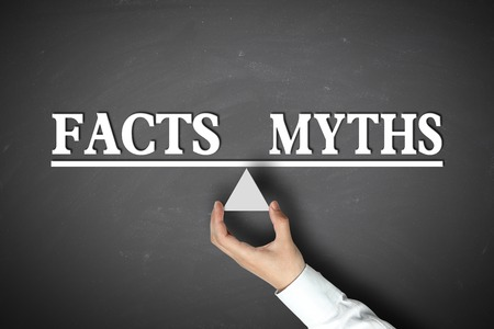 myths: Facts Myths Balance concept with scale holden by businessman hand against the blackboard background.