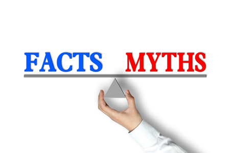 factual: Facts Myths Balance concept with scale holden by businessman hand isolated on white background.
