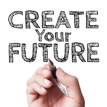and the future: Hand with pen writing the text Create your future on the transparent whiteboard.