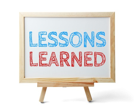 learned: Whiteboard with text Lessons learned isolated on white background. Stock Photo