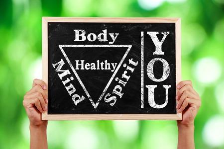 両手グリーンに対してあなたの体精神魂心健康的なテキストと黒板には、背景がぼやけています。