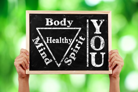 Hands holding blackboard with text You Body Spirit Soul Mind Healthy against green blurred background.