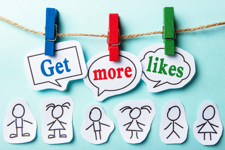 likes: Get more likes paper speech bubbles and some paper person under them. Stock Photo