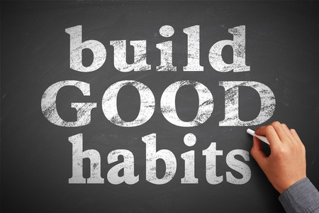 good habits: Hand with chalk is writing the concept of Build Good Habits on the blackboard. Stock Photo