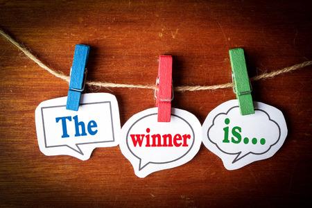 winner: El ganador es el discurso concepto burbujas del papel con la línea en el fondo de madera. Foto de archivo