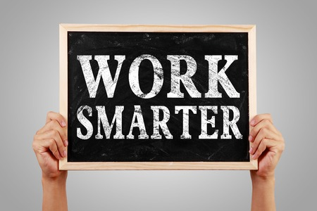 smarter: Hands holding blackboard with text Work Smarter against gray background. Stock Photo