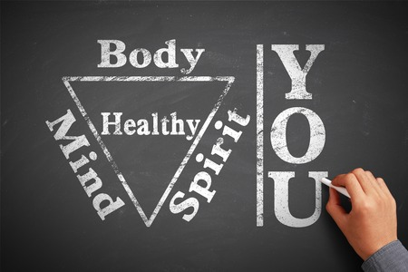 Hand with chalk is writing the concept of You Body Spirit Soul Mind Healthy on the blackboard. Stock Photo