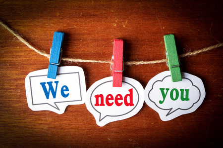 volunteering: We need you concept paper speech bubbles with line on the wooden background. Stock Photo