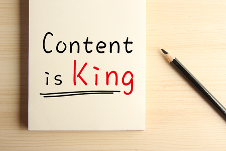outbound: Text Content is King with underline on the notebook with a pencil aside.