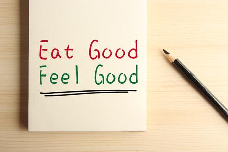 Text Essen gut Fühlen Sie sich gut mit Unterstrichen auf dem Notebook mit einem Bleistift beiseite.