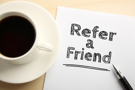 Text Refer a friend written on the white paper with pen and a cup of coffee aside.