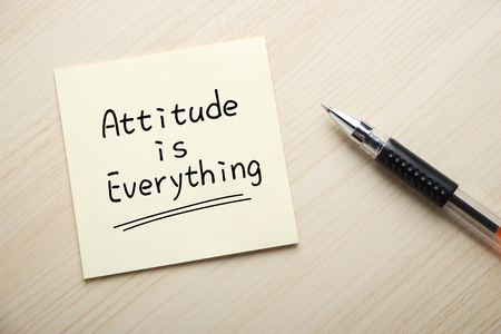 Text Attitude is Everything written on the sticky note with pen aside.