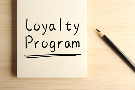 Text Loyalty Program with underline on the notebook with a pencil aside.
