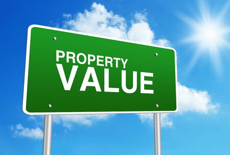 value: Green road sign with text Property Value is in front of the blue sunny background. Stock Photo