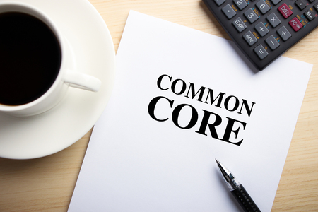 repeal: Text Common Core is on the white paper with coffee, calculator and ball pen aside.