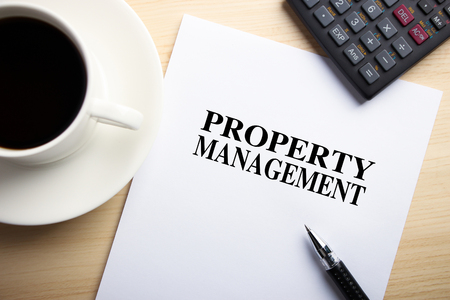property management: Text Property Management is on the white paper with coffee, calculator and ball pen aside.
