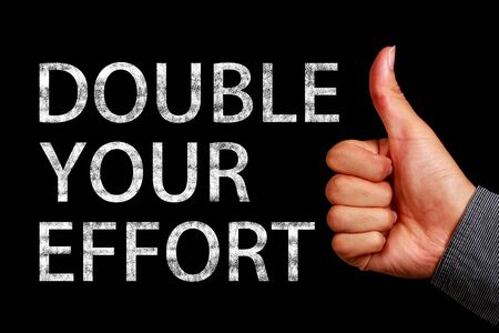 effort: Text Double Your Effort is written on the blackboard with thumb up hand aside.