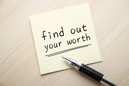find out: Text Find out Your Worth is written on the sticky note with ball pen aside.