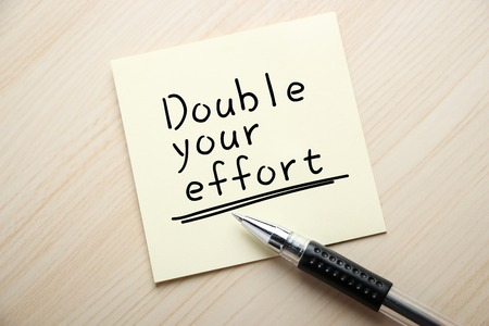 effort: Text Double Your Effort is written on the sticky note with ball pen aside. Stock Photo