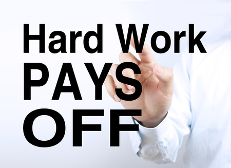 Businessman is pointing the text Hard Work Pays Off on the virtual transparent screen. Stock Photo