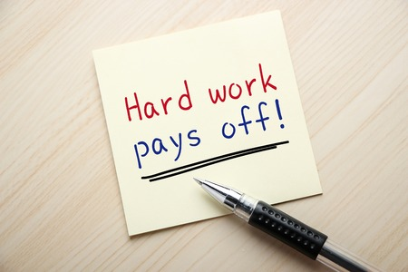 difficult period: Text Hard Work Pays Off is written on the sticky note with ball pen aside.