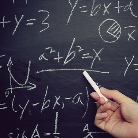 Teacher writing various high school maths formula on chalkboard. Archivio Fotografico