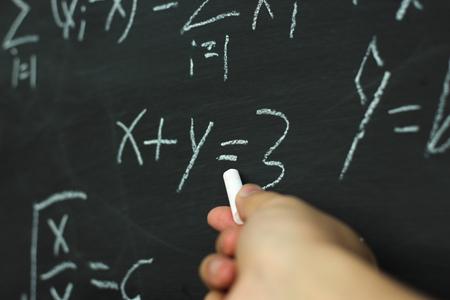 Teacher writing various high school maths formula on chalkboard. Standard-Bild