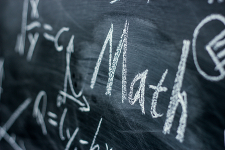 黒板の背景にいくつかの数学の数式と数学テキスト。